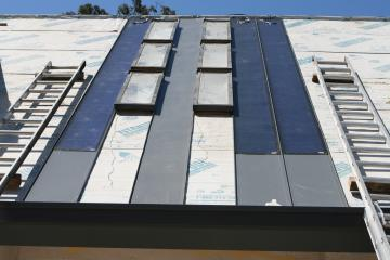 [First few standing seam metal roof panels in place]