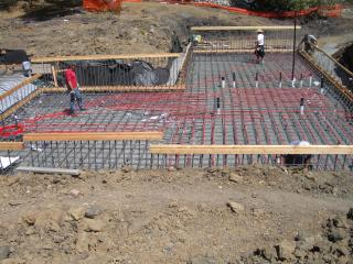 [Basement slab rebar with radiant heat tubes being laid]